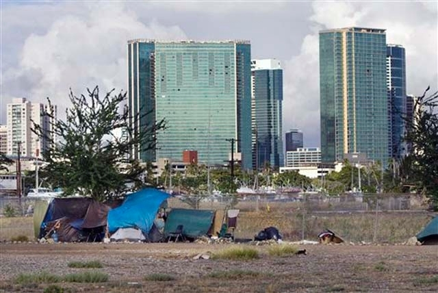 In this Monday, July 12, 2010 photo, the Honolulu skyline rises behind a homeless camp in an empty lot near Kaakako Park, in Honolulu.