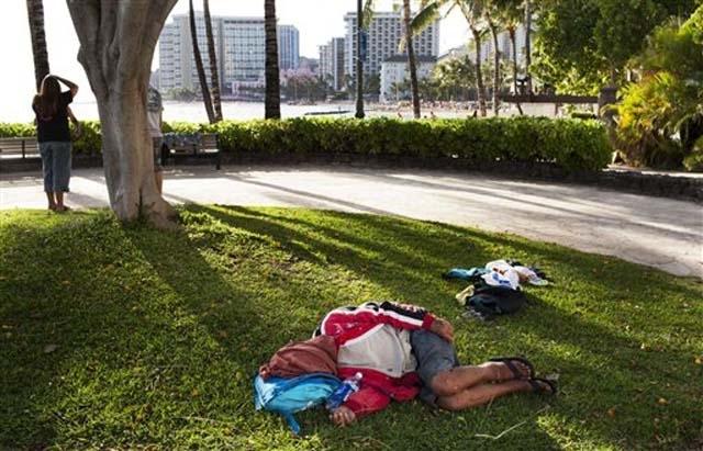 In this Friday, May 13, 2011 photo, a man sleeps on the ground near Waikiki Beach, in Honolulu.