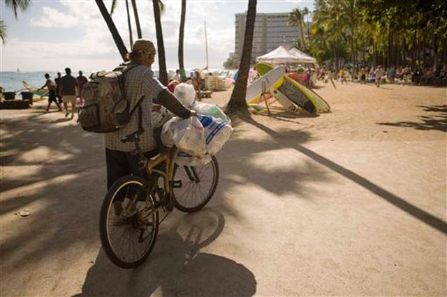 This July 12, 2010 photo shows a homeless man who goes by the name Guy West collecting cans on Waikiki Beach in Honolulu. Homelessness increased 15 percent on Oahu since last year according to a r ...
