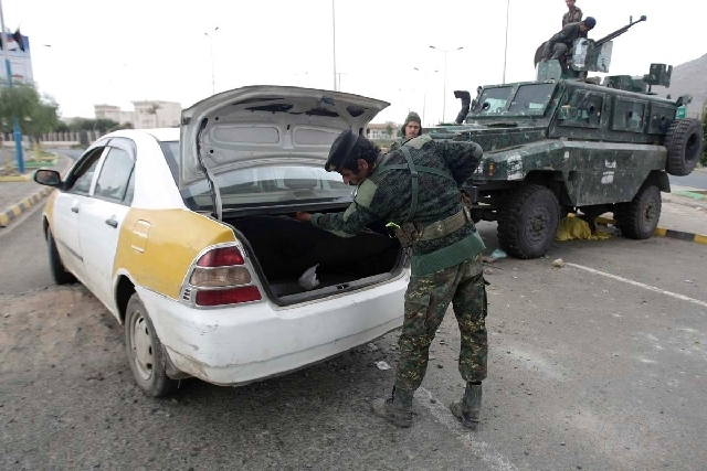 A policeman checks a car at a checkpoint near the U.S. embassy in Sanaa, Yemen, on Tuesday. The State Department on Tuesday ordered non-essential personnel at the U.S. Embassy in Yemen to leave th ...