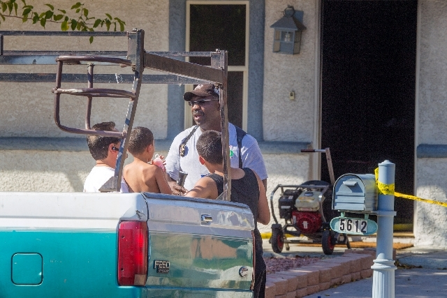 A  Las Vegas fire investigator talks to a family while standing by their home at 5612 Alta Drive which was gutted by fire on Tuesday. The fire, which started in the back patio at around 3 p.m., is ...