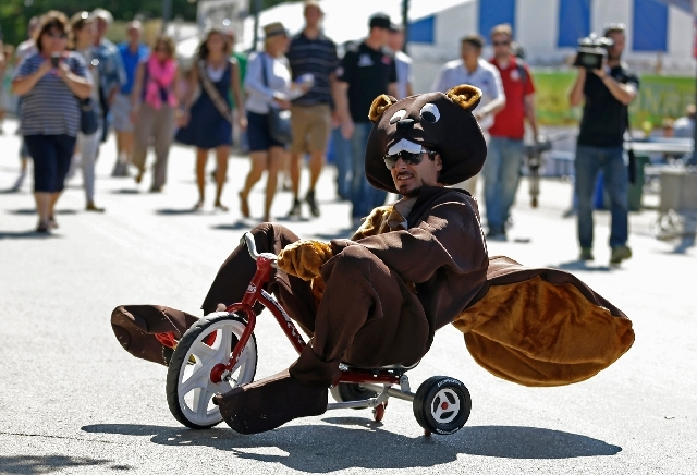 IndyCar driver Alex Tagliani, a Las Vegas resident, pedals a tricycle in a beaver costume Monday at the Indiana State Fair.