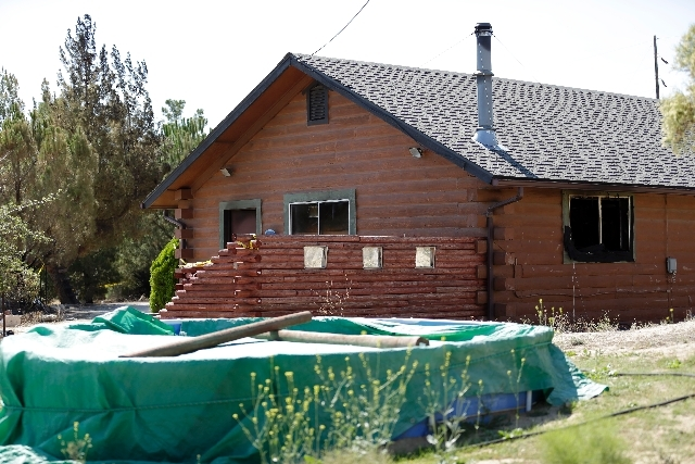 A partially burned home sits behind police tape Tuesday near the U.S.-Mexico border in Boulevard, Calif. The husband of a woman whose body was found in the house said Tuesday that he knew the man  ...
