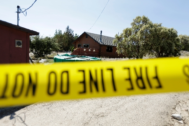 Police tape lines the perimeter of a partially burned home Tuesday, Aug. 6 near the U.S.-Mexico border in Boulevard, Calif. The husband of a woman whose body was found in the house said Tuesday th ...
