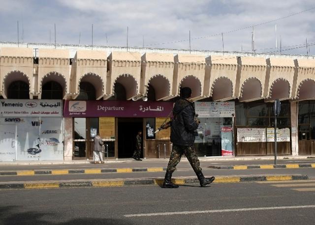A policeman walks as he secures the Sanaa International Airport, in Yemen.