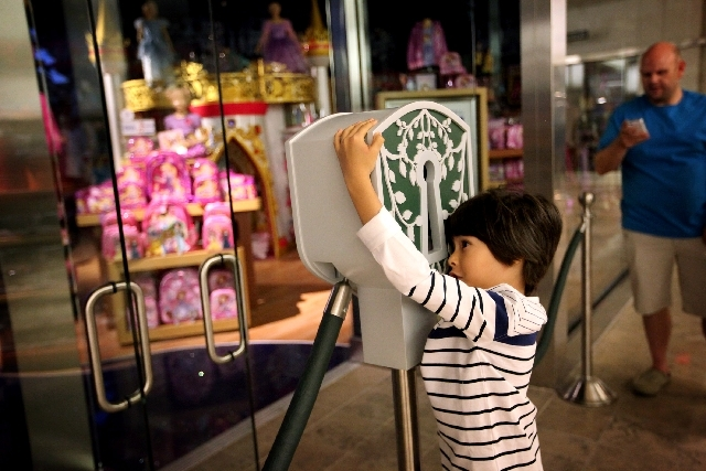 Six-year-old Hazza Alnahyan of Las Vegas hugs the keyhole to be ceremonially unlocked at the soft opening of the Disney Store at Fashion Show Mall in Las Vegas Wednesday.