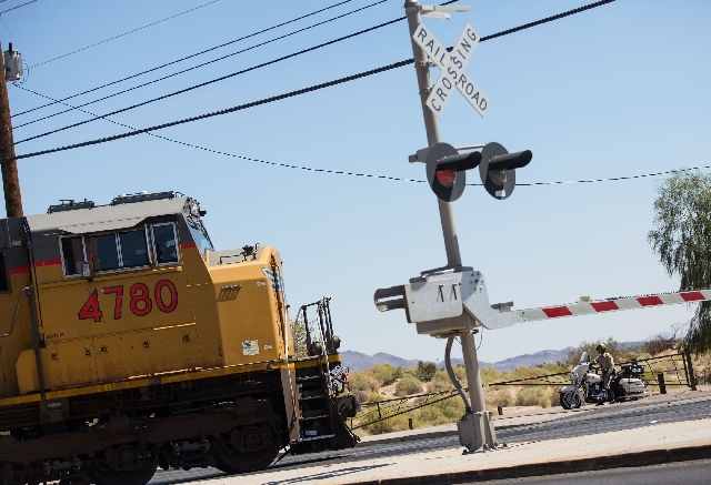 A police officer watches as a Union Pacific Railroad train passes Eastern Avenue on Wednesday. The violation for dashing past the flashing red lights can exceed $400.