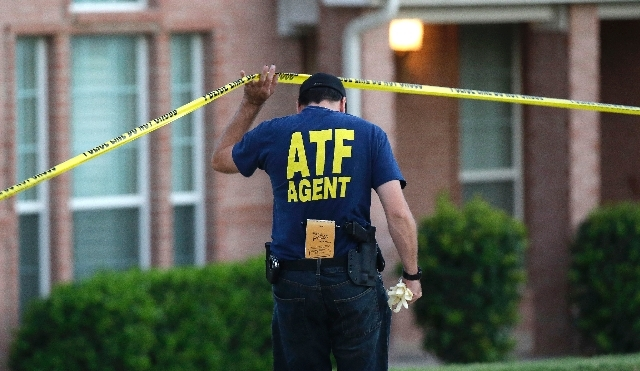 An ATF agent on Thursday walks toward one of the houses involved in the fatal shooting for four people in DeSoto, Texas, in south Dallas County on Wednesday night.