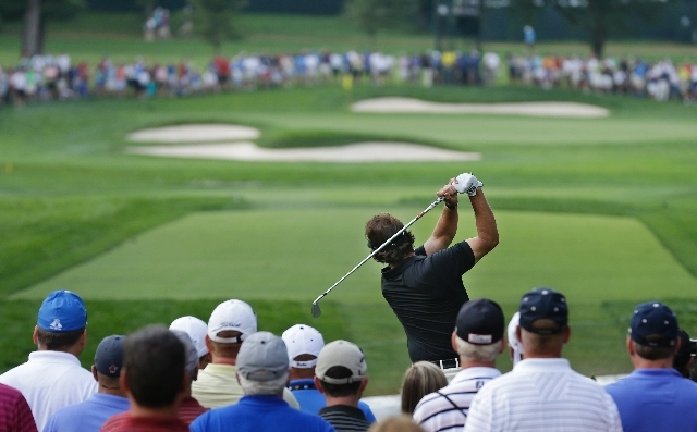 Phil Mickelson watches his tee shot on the 11th hole during the first round of the PGA Championship golf tournament at Oak Hill Country Club, Thursday in Pittsford, N.Y.