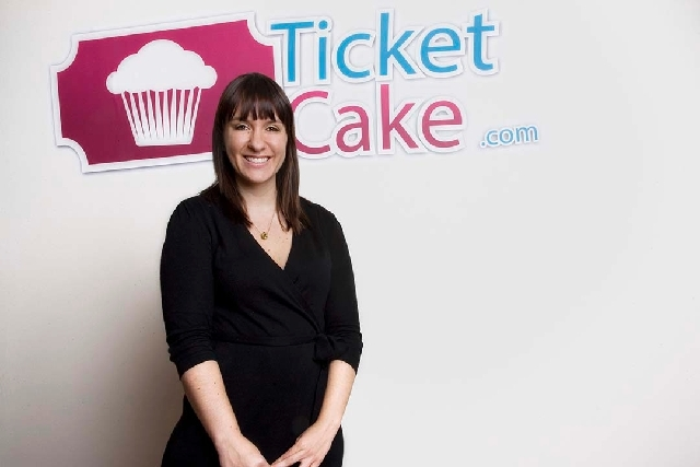 Jacqueline Jensen, founder and COO of Ticket Cake, poses Tuesday in front of the company logo in her office at 150 Las Vegas Blvd. North in Las Vegas on Tuesday.  Ticket Cake is a downtown-based t ...