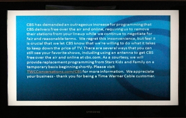 A television screen shows the CBS channel with an announcement by Time Warner Cable in Los Angeles.