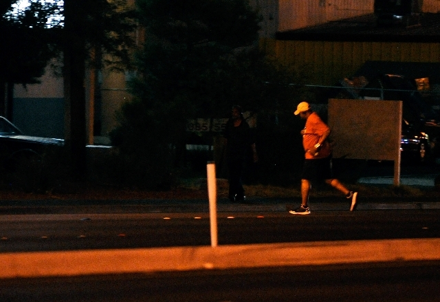 A pedestrian runs across Boulder Highway on Friday. Police say alcohol can impair pedestrians' judgment, leading them to cross a road in the wrong place or cross it against a stoplight.