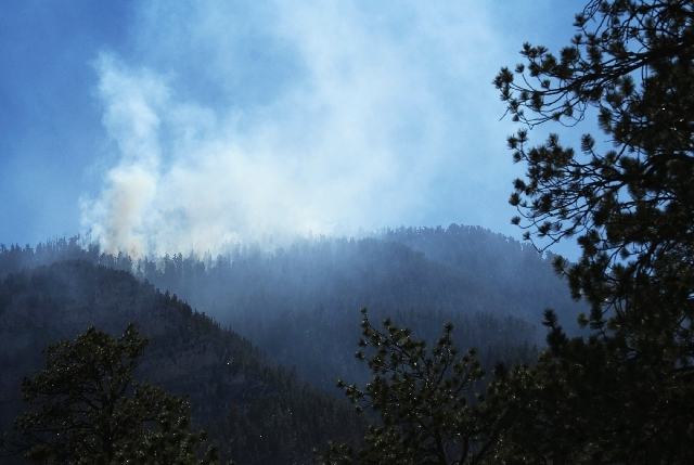 A hot spot from the still-burning Carpenter 1 Fire sends smoke into the sky on the south ridge of Kyle Canyon, just west of Griffith Peak, near Mount Charleston on Sunday. According to National Fo ...