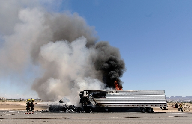 Clark County Firefighters work to extinguish a truck fire that erupted along the northbound side of I-15 just north of Blue Diamond Road on Monday