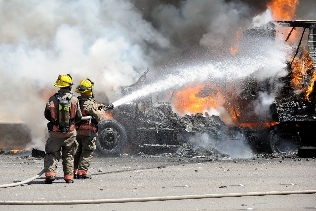 Clark County Firefighters work to extinguish a truck fire that erupted along the northbound side of I-15 just north of Blue Diamond Road on Monday.