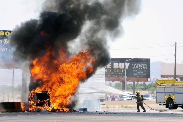 A Clark County firefighter works to extinguish a truck fire that erupted along the northbound side of I-15 just north of Blue Diamond Road on Monday.