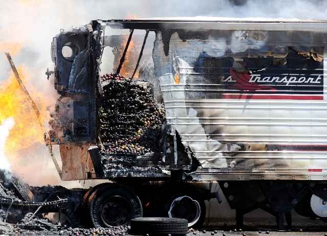 The contents of  a truck are exposed as it is on fire along the northbound side of I-15 just north of Blue Diamond Road on Monday.