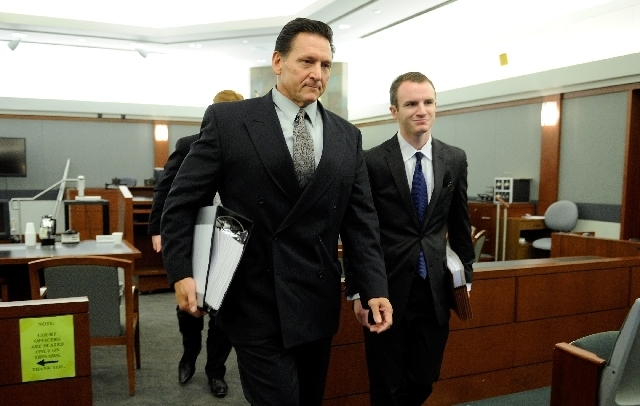 Family Court Judge Steven Jones, left, leaves District Judge Michael Villani's courtroom with Josh Reisman after a hearing at the Clark Country Regional Justice Center on July 26.
