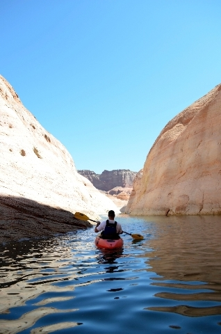 A kayaker glides along the surface of Lake Powell near Page, Ariz.