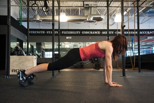 Begin in push-up position. Tighten the core and glutes and straighten the back.