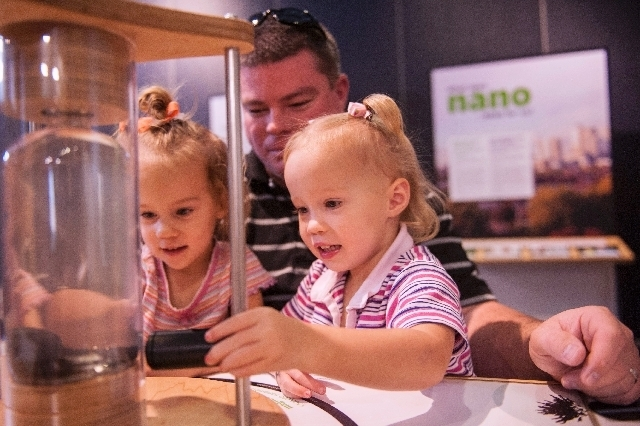 Ainsley Hardman, 2, left, plays with her father, Kyle, and twin sister Lydia at the Discovery Children's Museum.