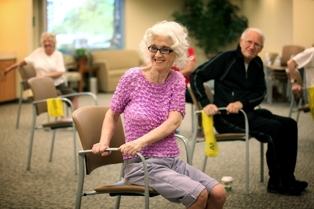 Agnes Firek, 70, front, exercises her back by twisting while seated in a chair.