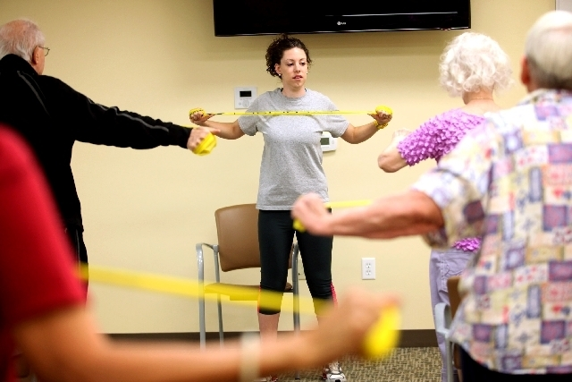 Instructor Alicia Fellows uses a resistance band while leading an exercise class.