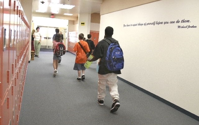 Students at Jerome Mack Middle School hike to class loaded with books and expectations for a new year.