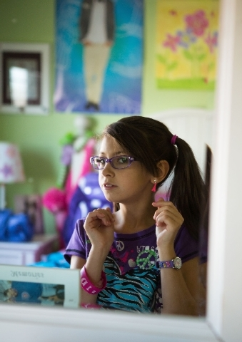 Sarah Timpa, 11, shows off her new school clothes and accessories at her Henderson home.