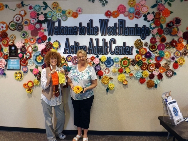 Organizer Diane Bush, left, and crocheter Mary Wehr-Clevenger show off a crocheted flower and squares in front of the yarn mural at a Yarn-a-Thon event Aug. 10 at the West Flamingo Senior Center,  ...