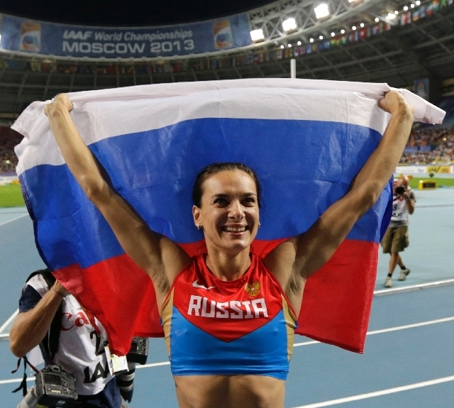 Russia's Yelena Isinbayeva poses with the national flag as she celebrates winning the gold medal in the women's pole vault final.