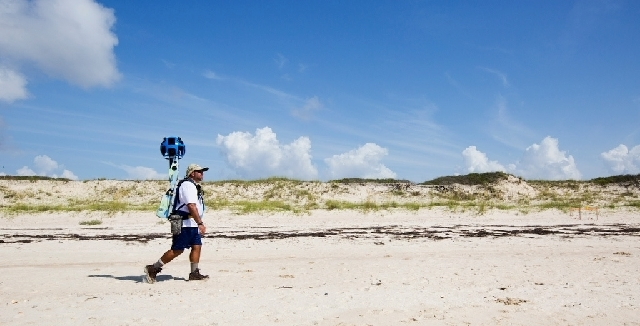 Gregg Matthews carries a Google street view camera as he walks recording St. George Island sand dunes in the Florida Panhandle.