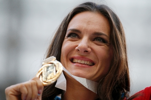Russia's Yelena Isinbayeva poses with her gold medal in the women's pole vault as she stands on the podium during the medal ceremony at the World Athletics Championships in the Luzhniki stadium  ...