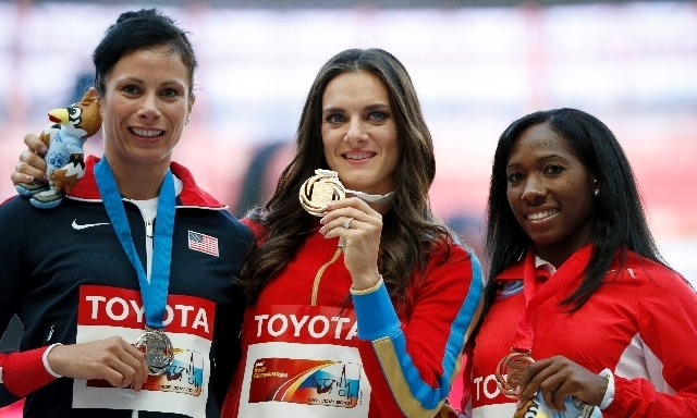 Russia's gold medal winner in the women's pole vault Yelena Isinbayeva is flanked by silver medal winner Jennifer Suhr of United States, left, and bronze medal winner Yarisley Silva of Cuba at t ...