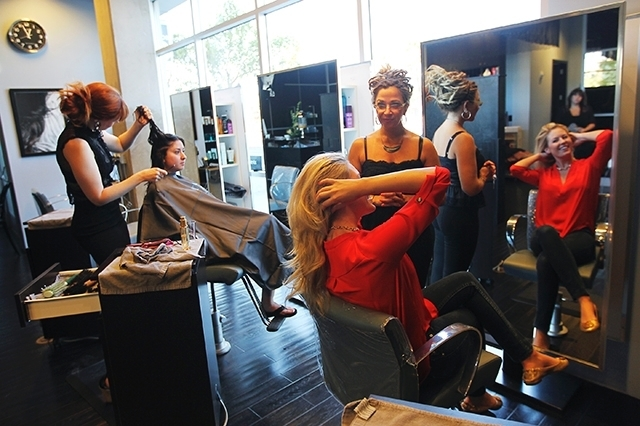Salon director Staci Linklater, standing right, and stylist Cassie Peters, far left, work with clients Aug. 10 at Globe Salon.