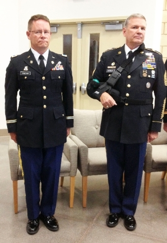 Nevada Army National Guard Col. Michael Hanifan, left, stands at attention next to state Command Sgt. Maj. Daryl Keithley during an officer candidate graduation ceremony Aug. 9, at the North Las V ...