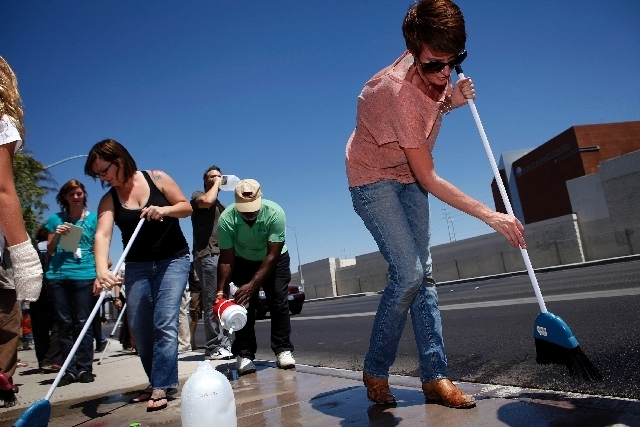 Jen Harney uses a broom and water to clean  up sidewalk chalk in front of the Las Vegas police headquarters in Las Vegas on Saturday. A group of people organized by Harney were in front of the hea ...