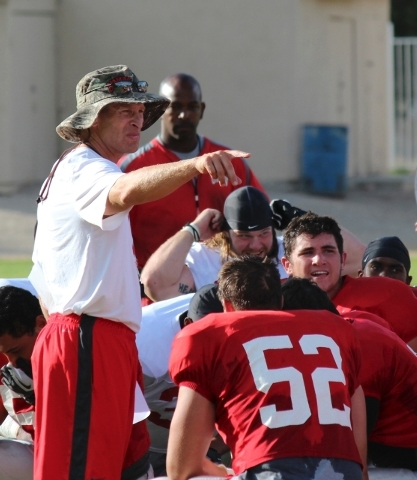 UNLV coach Bobby Hauck, above, issues instructions to the Rebels' defense, including freshman linebacker Kyle Anderson (52), during Saturday's scrimmage in Ely.