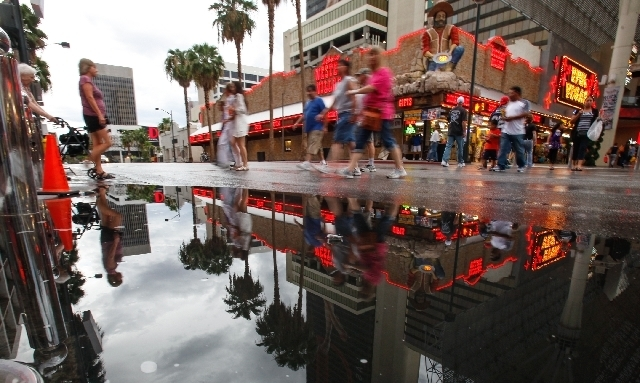 People cross Las Vegas Boulevard around the Fremont Street Experience area in downtown Las Vegas where heavy rains passed by on Sunday