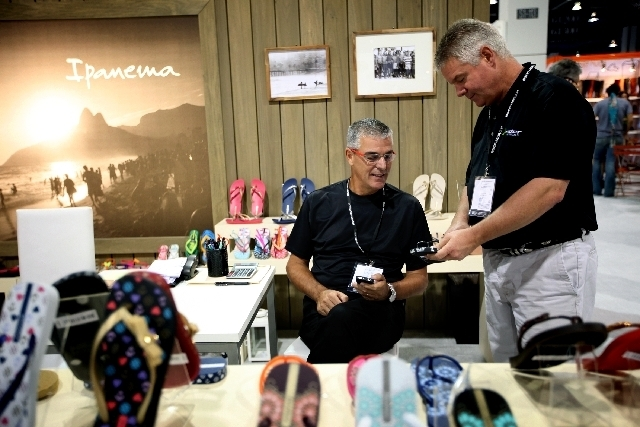 Angelo Daros, left, of Orlando, Fla., and Russ Ford of Knoxville, Tenn., talk shoes Monday at the Ipanema booth at the Magic Market Week fashion convention at the Las Vegas Convention Center. Daro ...