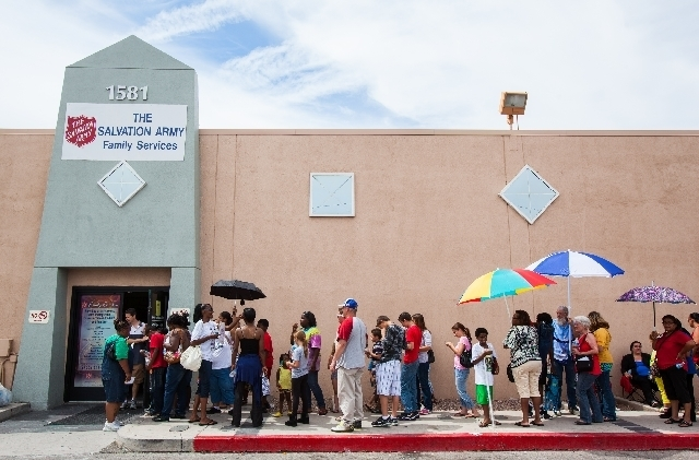 People wait in line to enter the Salvation Army Family Services Office on Monday to get free backpacks, school supplies, haircuts and immunizations.