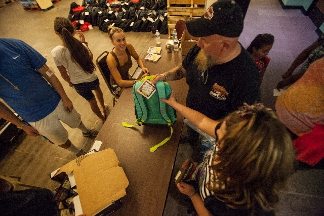 Ten-year-old Shelbie Rae Shaver, lower right, gets a backpack with her father, James, during an event Monday at the Salvation Army Family Services Office, 1581 N. Main St., offering free backpacks ...