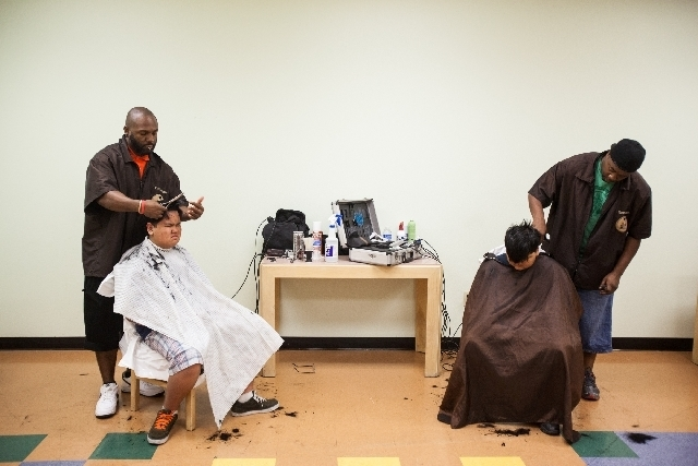 House of Fades barbers Eric Young, left, and Tray Mays, give haircuts to brothers Cyrus Tranate, 10, right, and Ethan, 11, during an event at Salvation Army Family Services Office on Monday. The e ...