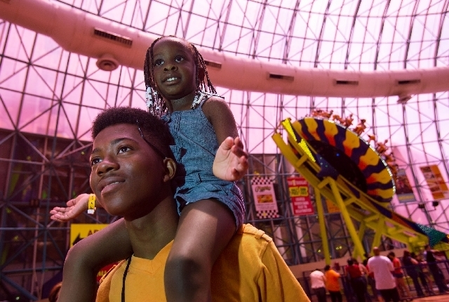 Pierre Cooley, 18, and niece Jasmine Driver, 3, watch a magic show at the Adventuredome theme park inside Circus Circus earlier this month while visiting from Chicago. The attraction is celebratin ...