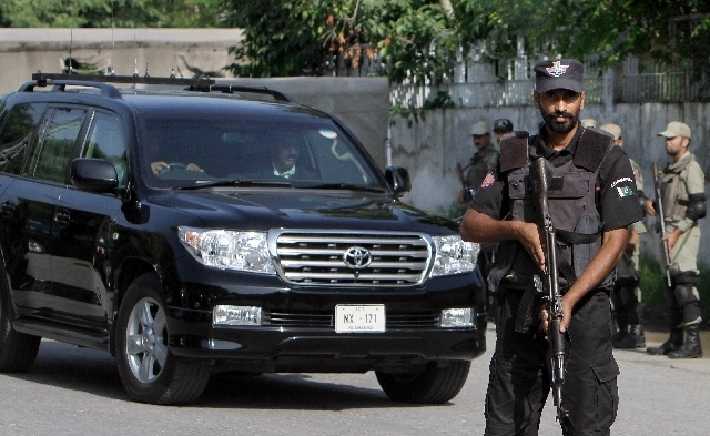 A Pakistani police commando stands guard as a vehicle carrying former President and army chief Pervez Musharraf arrives to appear at an anti-terrorism court Tuesday in Rawalpindi, Pakistan. A Paki ...