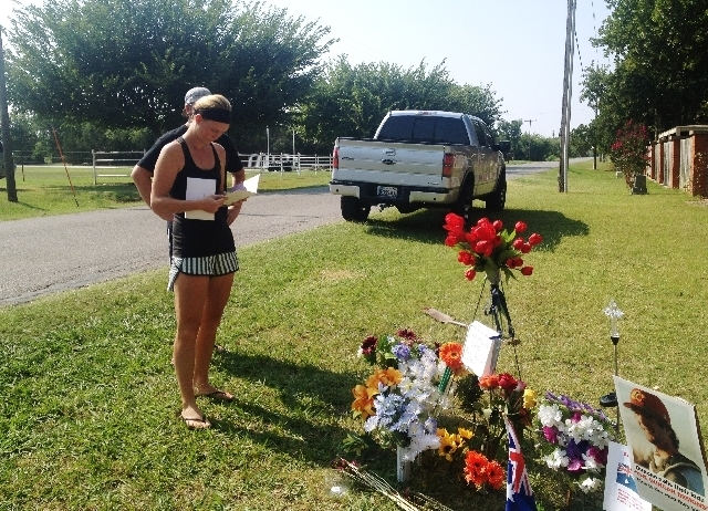 Sarah Harper, Christopher Lane's girlfriend, stands beside a memorial Tuesday along the road where police say Lane, an Australian baseball player, was shot and killed Friday by three teenagers w ...