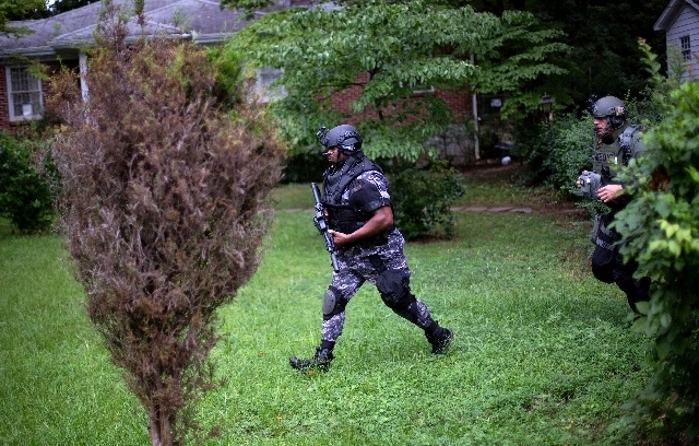 ---Dekalb County Police SWAT officers run though the front yard of a home toward Ronald E. McNair Discovery Learning Academy after reports of a gunman entered the school, Tuesday, Aug. 20, 2013, i ...