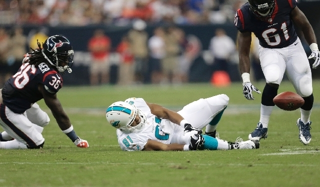Dolphins tight end Dustin Keller grabs his right knee Saturday after being hit by Texans safety D.J. Swearinger, not shown, in Miami's 24-17 exhibition loss. Keller was diagnosed with three torn  ...