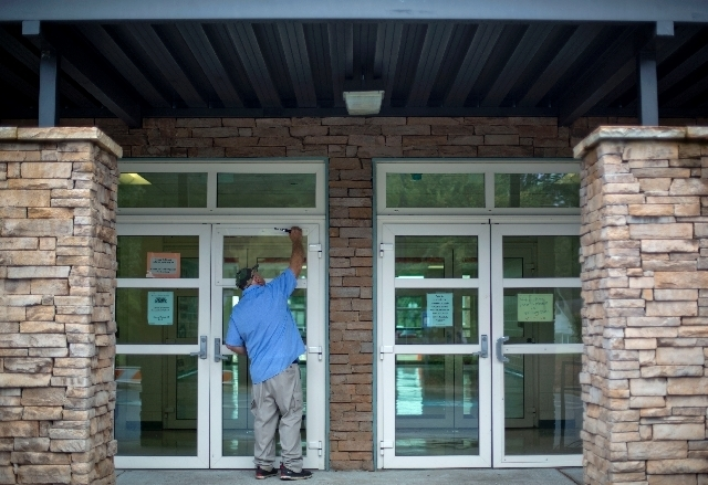 Carpenter William Brooks secures a piece of plexiglass to the front door of the Ronald E. McNair Discovery Learning Academy where a glass panel was shot out during an exchange of gunfire Tuesday b ...