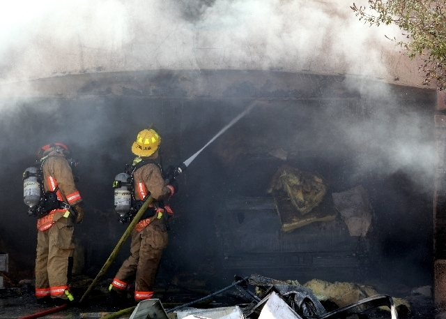 Las Vegas firefighters extinguish a fire that started in a garage at 2312 Sun Cliffs St. in Sun City on Wednesday morning. (Justin Yurkanin/Las Vegas Review-Journal)